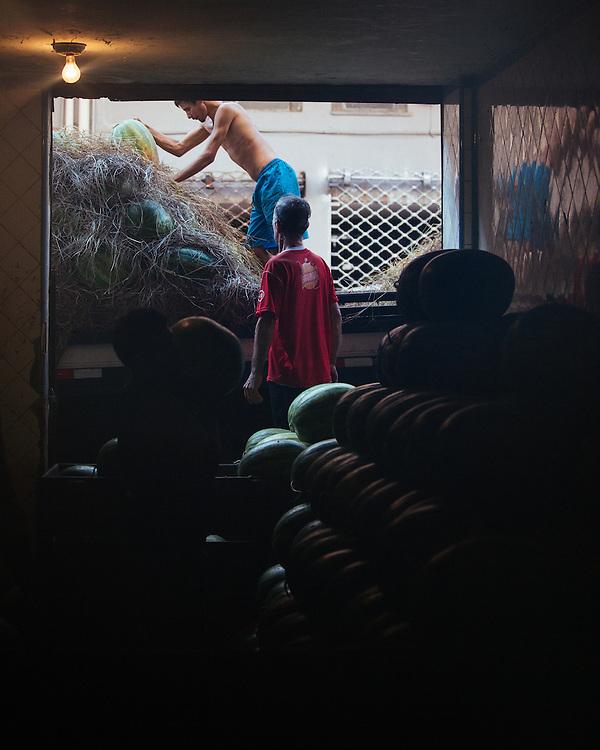 Men store watermelons at Rio's CADEG Market.