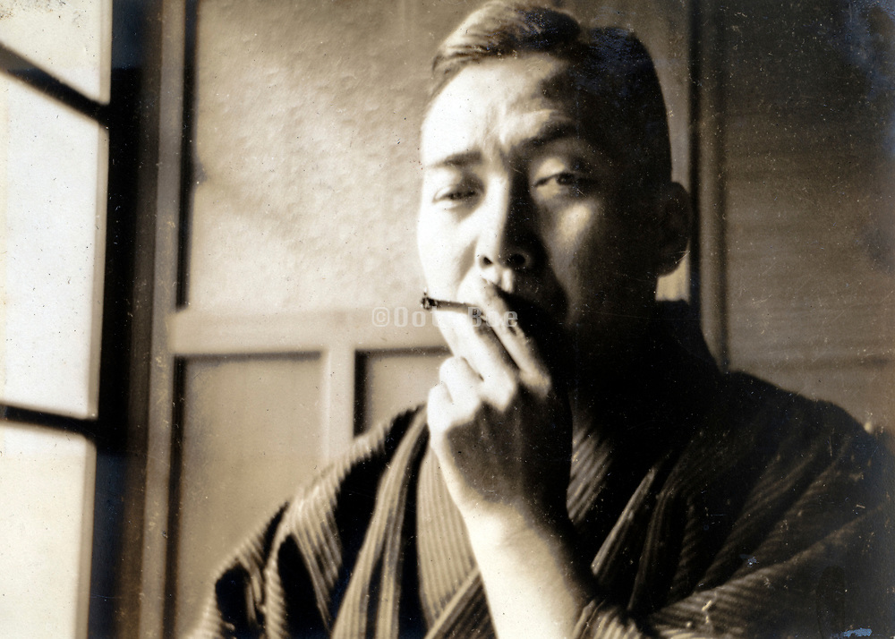 casual portrait of a man smoking indoors Japan ca 1950s