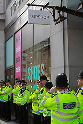 © Licensed to London News Pictures. 01/05/2012. London, UK. Police officers protecting the front of Top Shop on Oxford Street, after May Day protesters caused the closure of other shops on Oxford street after trying to occupy them. They were calling for the end of mandatory non paid work placements. Photo credit : James Gourley/LNP