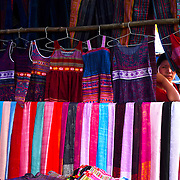 Woman peeping through fabrics at North Vietnam market