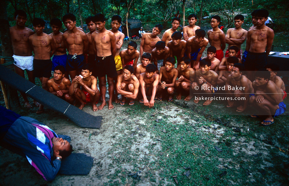 Young Nepali boys watch how to perform sit-ups in Himalayas, hoping to be recruited for the Gurkha Regiment in the British army. This is part of a tough endurance series to find physically perfect specimens for British army infantry training. They will need to perform 25 straight-kneed sit-ups at a 45° slant both within 60 seconds to pass. 60,000 boys aged between 17-22 (or 25 for those educated enough to become clerks or communications specialists) report to designated recruiting stations in the hills each November, most living from altitudes ranging from 4,000-12,000 feet. After initial selection, 7,000 are accepted for further tests from which 700 are sent down here to Pokhara in the shadow of the Himalayas. Only 160 of the best boys succeed in the journey to the UK. The Gurkhas have been supplying youth for the British army since the Indian Mutiny of 1857.