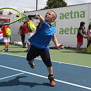 August 16, 2014, New Haven, CT:<br /> A young fan hits a tennis ball during a tennis clinic in the AETNA FitZone as part of Kids Day on day three of the 2014 Connecticut Open at the Yale University Tennis Center in New Haven, Connecticut Sunday, August 17, 2014.<br /> (Photo by Billie Weiss/Connecticut Open)