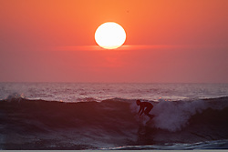 © Licensed to London News Pictures. 26/03/2020. Wadebridge, UK. A surfer catches a wave at Constantine Bay beach, Cornwall, during sunset this evening. British Prime Minister Boris Johnson yesterday ordered a lockdown to slow the spread of Coronavirus (COVID-19) across the country. Photo credit : Tom Nicholson/LNP