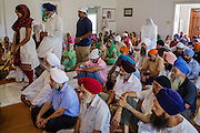 12 AUGUST 2012 - PHOENIX, AZ:  Members of the Phoenix Sikh community enter the Gurdwara to make an offering to the Guru while others pray during Sunday services at the Guru Nank Dwara Ashram Sikh temple in central Phoenix. Guru Nank Dwara Ashram is the oldest of three Sikh temples in the Phoenix area. There are about 1,500 Sikh families in the area. Memorials have been held throughout the week to honor the Sikhs killed in the mass shooting in Wisconsin last week. Sunday's service included several mentions of the massacre and was attended by a number of people active in the Phoenix interfaith community.   PHOTO BY JACK KURTZ