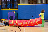 Newburgh, New York - Children play with a tube during the YMCA's Family Night at the Newburgh Armory Unity Center on March 27, 2015.