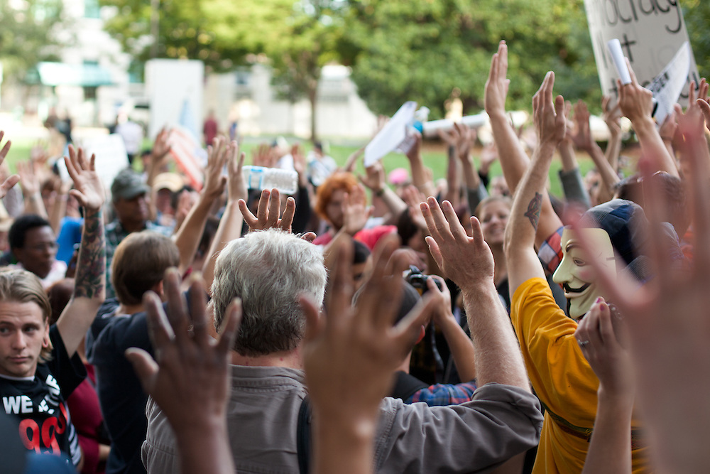 People go over the hand signals at a General Assembly before they marched to Bank Of America Headquarters.