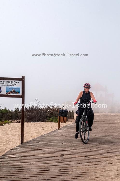 woman cycles on the Eurovelo 1 Atlantic coast route Near Porto, Portugal. The Atlantic Ocean coast on the left