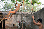 Indian Khusti wrestlers practice by climbing ropes at a wrestling Akhara in New Delhi, India. <br /> Pehlwani, or kusti is a form of wrestling from South Asia. It was developed in the Mughal Empire by combining native malla-yuddha with influences from Persian koshti pahlavani. A practitioner of this sport is referred to as a pehlwan.