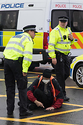 Colnbrook, UK. 27th September, 2021. Metropolitan Police officers monitor an Insulate Britain climate activist glued onto a slip road from the M25 at Junction 14 close to Heathrow airport as part of a campaign intended to push the UK government to make significant legislative change to start lowering emissions. The activists are demanding that the government immediately promises both to fully fund and ensure the insulation of all social housing in Britain by 2025 and to produce within four months a legally binding national plan to fully fund and ensure the full low-energy and low-carbon whole-house retrofit, with no externalised costs, of all homes in Britain by 2030.