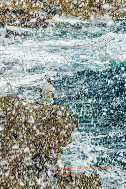 Sea Spray: A man sits precariously above a crashing surf fishing for his evening's meal, Baracoa Cuba.