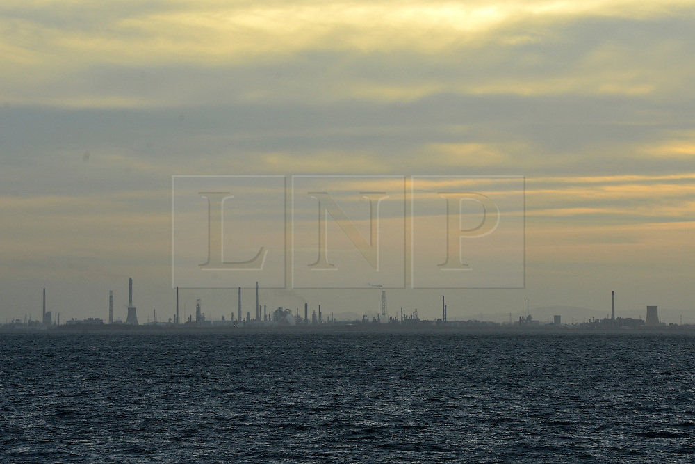 © Licensed to London News Pictures. 15/12/2013. Liverpool, UK. Stanlow Oil Refinery seen in the distance. People walk and play in the windy weather at Otterspool Promenade in Liverpool Merseyside today, 15th December 2013 . Photo credit : Stephen Simpson/LNP