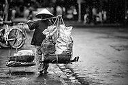 Old vietnamese woman carrying jute bags on her yoke by a rainy day in Hoi An, Vietnam, Asia
