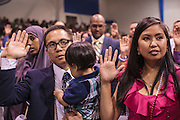 04 JULY 2012 - PHOENIX, AZ:  LUIGE DEL PUERTO holds his son, SOL ELIJAH DEL PUERTO, while they and his wife, PEARL DEL PUERTO take the oath of citizenship as they are naturalized US citizens Wednesday. They are originally from the Philippines. About 250 people, from 62 countries, were naturalized as US citizens during the 24th Annual Fiesta of Independence naturization ceremony at South Mountain Community College in Phoenix Wednesday. The ceremony was presided over by the Honorable Roslyn O. Silver, Chief United States District Court Judge.   PHOTO BY JACK KURTZ