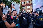 A protester yells at the police with a picture of Minneapolis man, George Floyd, who died in police custody, outside the Oakland Police Department on May 29, 2020.