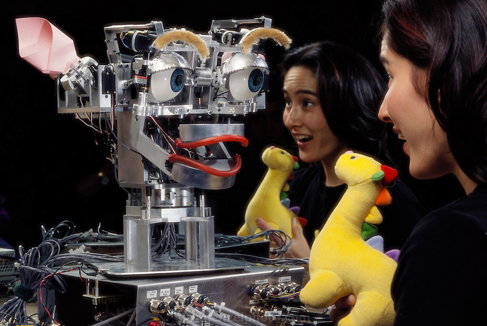 Kismet is a complex autonomous robot developed by Dr. Cynthia Breazeal, at the time of this image a doctoral studies student at the MIT Artificial Intelligence Lab under the direction of Rod Brooks. Breazeal's immediate goal for Kismet is to replicate and possibly recognize human emotional states as exhibited in facial expressions. Breazeal has located the most important variables in human facial expressions and has mechanically transferred these points of expression to a robotic face. Kismet's eyelids, eyebrows, ears, mouth, and lips are all able to move independently to generate different expressions of emotional states.
