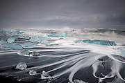 Icebergs in the waves on Jökulsárlón beach, in south-east Iceland. They float down from the nearby river, after calving from the Breiðamerkurjökull glacier. Each day the river and tide bring in new icebergs, which then get smashed by the waves against the beach.