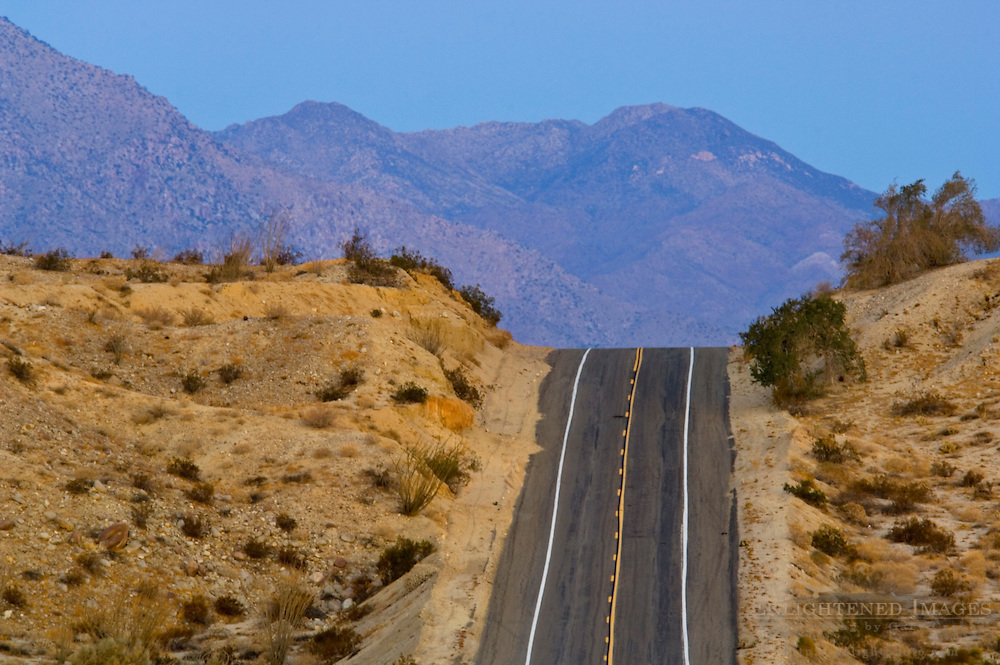 Two lane desert road crests over a hill, Anza Borrego Desert State Park, San Diego County, California