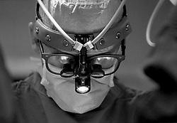 Stock photo of a surgeon wearing medical binoculars