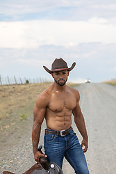hot shirtless muscular cowboy holding a saddle on a dirt road