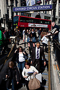 Shoppers in central London descend into Oxford Circus tube station. UK.As a worker hands out free copies of the newspaper The Evening Standard, this is a busy part of the daily commute.