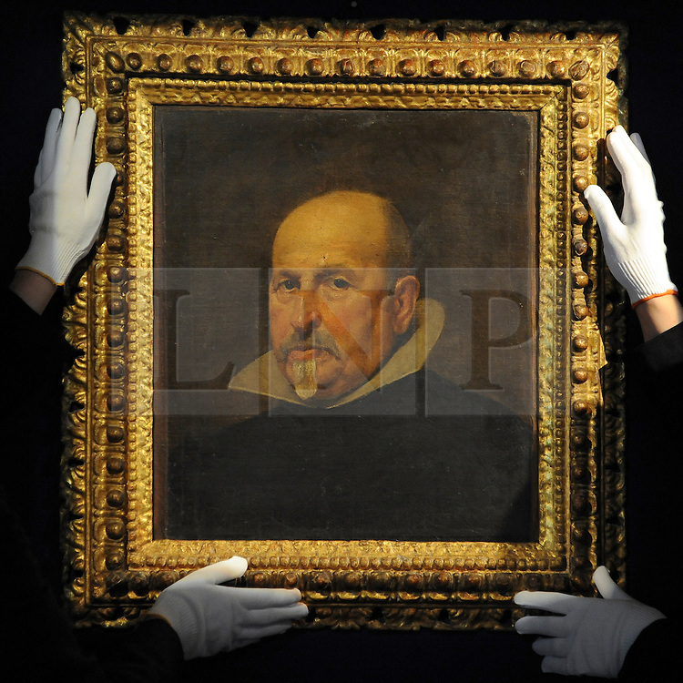 35559258© Licensed to London News Pictures. 27/10/2011. London, UK. Members of Bonhams staff hold the painting. A previously unknown portrait by the Spanish artist Diego Rodriguez de Silva y Velazquez (1599-1660) is unveiled at Bonhams Auction House in London today, 27th October. The work is a portrait of a gentleman in a black tunic and white collar and is expected to fetch 2-3million GBP.  Photo: Stephen Simpson/LNP