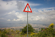 Warning sign of risk on the western slope of Vesuvius with the urban sprawl of Naples in the distance. The national emergency plan to protect the inhabitants from a possible eruption of the Vesuvius area has as its baseline the explosive event of 1631. Drafted by the scientific community has identified three areas with different hazard defined: the red zone, yellow zone and the blue zone. The red zone is the area immediately surrounding the volcano, and is in greater danger as potentially subject to invasion by pyroclastic flows, From the Introduction page of the book 'Risk Wise: Nine Everyday Adventures' by Polly Morland (Allianz, The School of Life, Profile Books, 2014).