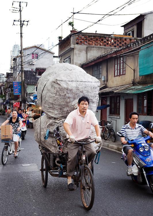 China, Shanghai,  27 aug 2010.Een fietscourier op een driewieler met een enorme last achterop. Alhoewel er ook veel welvaart is, wordt er ook nog veel slecht betaald en zwaar werk verricht door mensen die daar waarschijnlijk maar een schijntje mee verdienen. Maar ze verdienen tenminste iets...Foto (c)  Michiel Wijnbergh