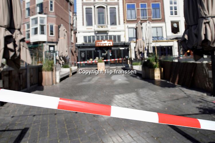Nederland, Nijmegen, 22-3-2020  Om te voorkomen dat bezoekers aan de binnenstad op de lege terrassen gaan zitten  spannen medewerkers van bureau toezicht op aanwijzing van burgemeester Hubert Bruls afzetlint voor de terrassen. Foto: Flip Franssen