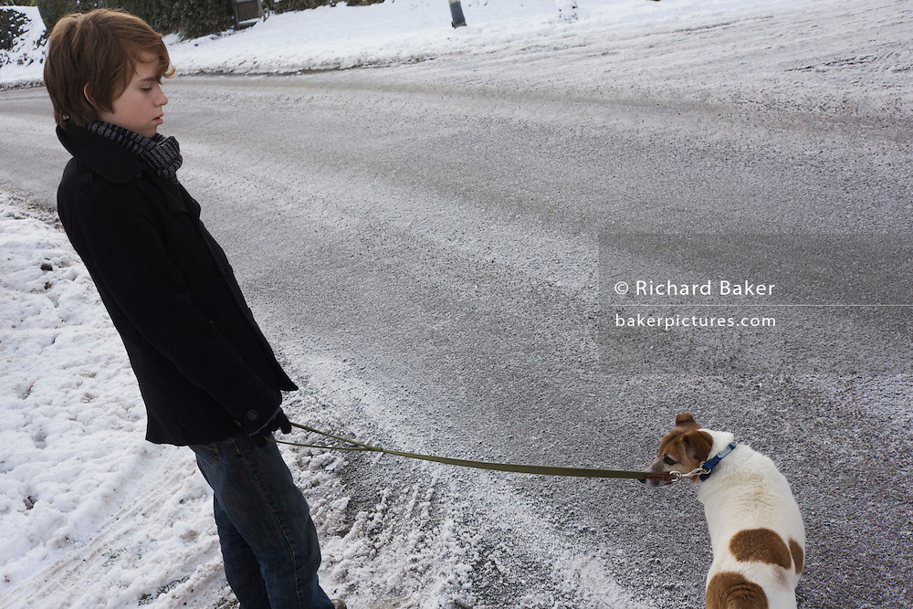 Young 12 year-old boy about to cross icy road to walk a pet Terrier dog during wintry snows.