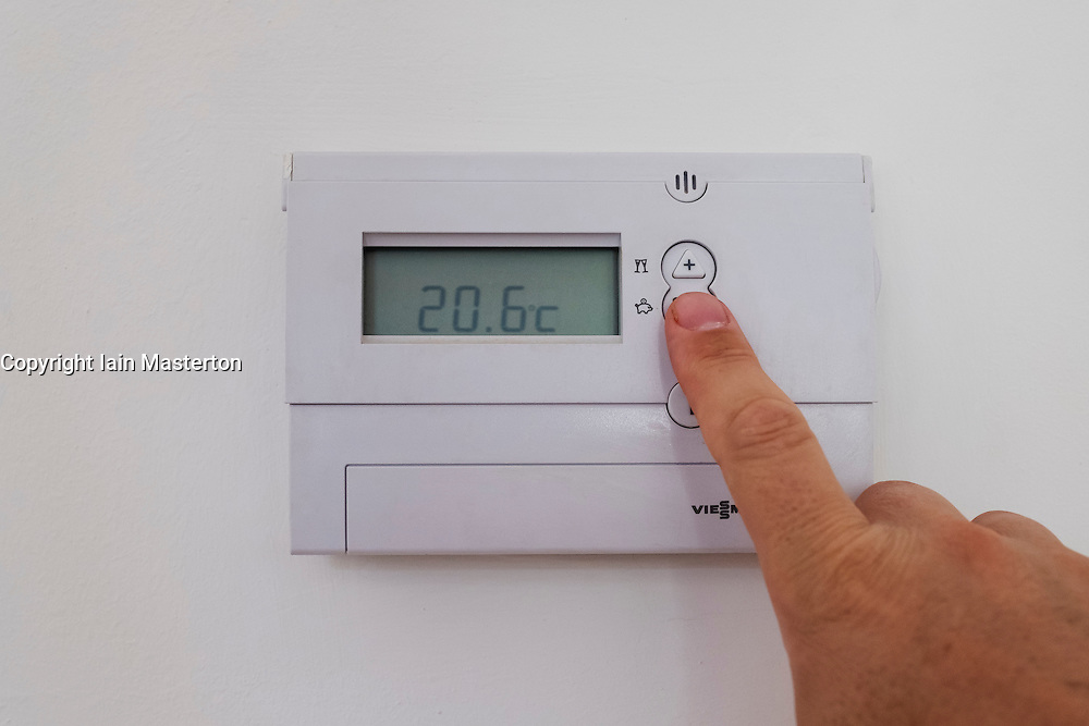 Man adjusting home central heating thermostat to lower temperature and save energy and money.