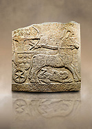 Photo of Hittite relief sculpted orthostat stone panel of Long Wall Limestone, Karkamıs, (Kargamıs), Carchemish (Karkemish), 900 -700 B.C. Anatolian Civilisations Museum, Ankara, Turkey<br /> <br /> Chariot. One of the two figures in the chariot holds the horse's headstall while the other throws arrows. There is a naked enemy with an arrow in his hip lying face down under the horse's feet. It is thought that this figure is depicted smaller than the other figures since it is an enemy soldier. The lower part of the orthostat is decorated with braiding motifs.<br /> <br /> On a brown art background. .<br />  <br /> If you prefer to buy from our ALAMY STOCK LIBRARY page at https://www.alamy.com/portfolio/paul-williams-funkystock/hittite-art-antiquities.html  - Type  Karkamıs in LOWER SEARCH WITHIN GALLERY box. Refine search by adding background colour, place, museum etc..<br /> <br /> Visit our HITTITE PHOTO COLLECTIONS for more photos to download or buy as wall art prints https://funkystock.photoshelter.com/gallery-collection/The-Hittites-Art-Artefacts-Antiquities-Historic-Sites-Pictures-Images-of/C0000NUBSMhSc3Oo