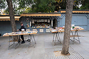 A man on a scooter stops to look at books on one of the many book stalls on the 30th of October 2019 down the Calle Claudio Moyano, Madrid, Spain.