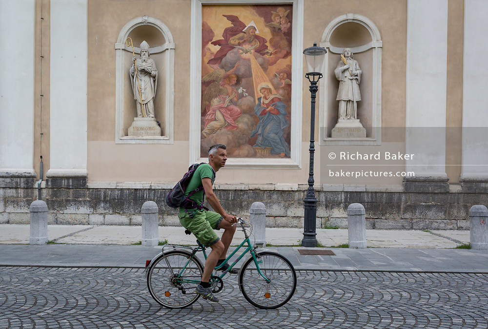 A cyclist rides past a mural and sculpture outside Cathedral of saint Nicholas in the Slovenian capital, Ljubljana, on 28th June 2018, in Ljubljana, Slovenia. Ljubljana is a small city with flat terrain and a good cycling infrastructure. It was featured at eighth on the 'Copenhagenize' index listing the most bike-friendly cities in the world though bike theft is prevalent.