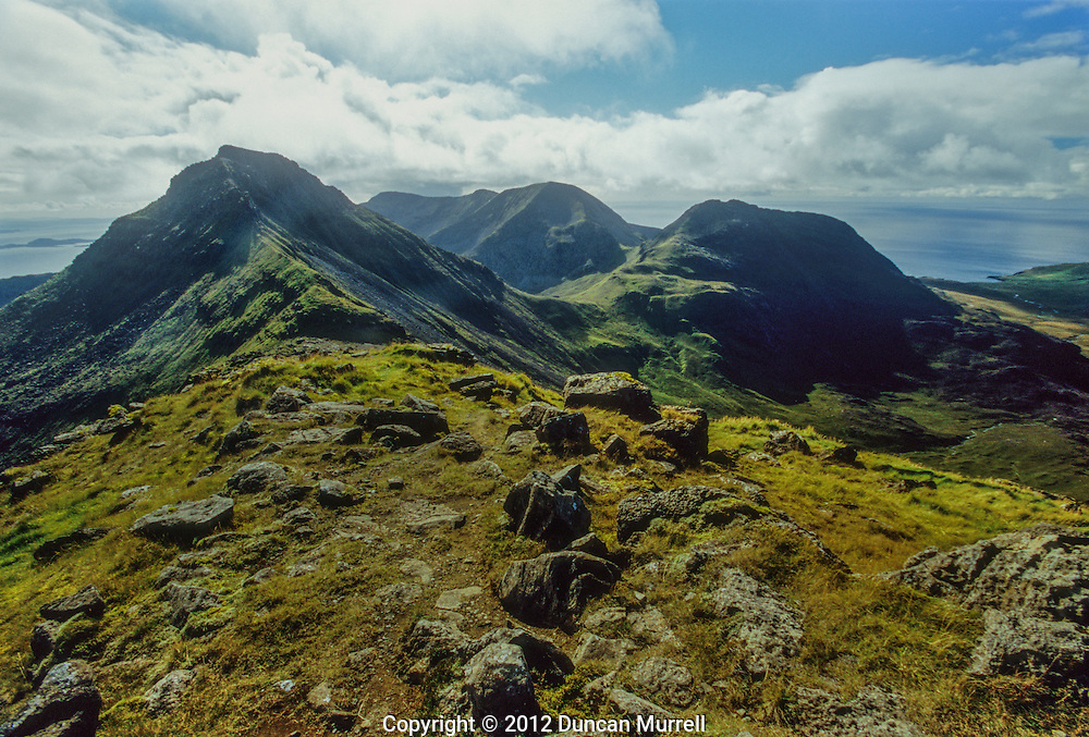 The main range of hills on Rum are called the Cuillin in the south of the island. They are rocky peaks of basalt and gabbro that are part of a core of a deeply eroded volcano that was active in the Paleogene era 66 – 23 million years ago. This view is looking towards Askival, 812 metres, and Ainshval, 778 metres, from Hallival. Hallival and Askival are formed from layered igneous rocks that accumulated at the base of a magma chamber. The chamber eventually collapsed, forming a caldera (crater). There are near vertical intrusions of basalt on the northwest coast, created by basaltic magma forcing its way into fissures in the pre-exiting rock.<br /> I hiked from Kinloch and up along the Cuillin from Hallival to Ainshval, which included some very steep and challenging scrambling on all fours, and then along a long undulating ridge with a fantastic view out across the sea, before descending down towards Glen Harris to the far right of this photo. It was unquestionably one of my favourite hikes that I have ever done anywhere in the world, with absolutely stupendous views in all directions across the island and out across the sea. I was travelling light, and I knew that I only had a limited amount of time to complete the circuit back to Kinloch, so it became an exhilarating sprint across the challenging terrain that kept my adrenaline pumping all the way. It takes pride of place in my top ten hikes in the world that I would like to redo one day.