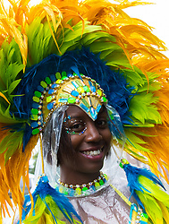 London, August 31st 2015. A woman's head dress brightens up the overcast day as revellers ignore the inclement weather to enjoy day two of the Notting Hill Carnival.