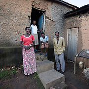 CAPTION: Scholastic stands with Jeremie and two of their children outside the house that they now own. When Jeremie was in prison and Scholastic was away in the hospital, their home was looted by robbers and Scholastic returned to a house that had been badly vandalised. At that time, the family lived in a building that belonged to the wider family as a whole, which could not be considered a permanent living arrangement as others in the extended family could ask them to leave at any time. However, her immediate family did have a right to one portion of the house, and could opt to pay other family members to buy out the other portions. Thus, they were able to gain full ownership of the house in this way in 2012, thanks to money generated from participation in the Graduation Programme. LOCATION: Kabuga Village, Gafumba Cell, Rusatira Sector, Huye District, South Province, Rwanda. INDIVIDUAL(S) PHOTOGRAPHED: From left to right: Scholastic Mukamuganga, Henriette Ingabire, Marie Besaie Niyinshubije and Jeremie Nyabibona.