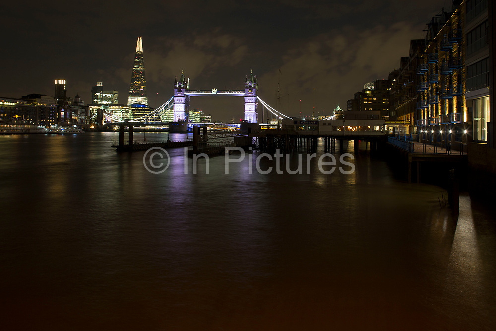 Long exposure night view of Tower Bridge and the skyline including the Shard over the River Thames in London, England, United Kingdom.