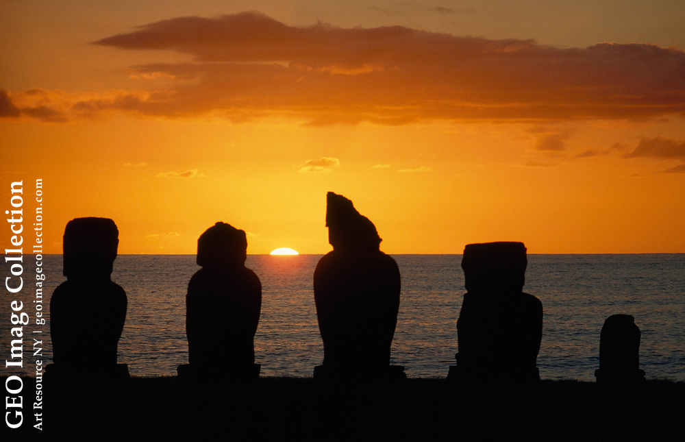 Five ancient statues are silhouetted against a sunset sky.