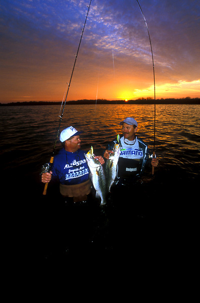 Stock photo of two professional fishermen showing off their catch at sunset