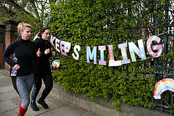 """© Licensed to London News Pictures. 01/04/2020. London, UK. Women jog past a 'KEEP SMILING"""" hand painted sign displayed outside a school in north London. Rainbows are used as a symbol of peace and hope. Photo credit: Dinendra Haria/LNP"""