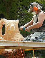 """Paul Stark of Oregon Studios carves a bear outside his workshop in Bethel on Aug. 8, 2013. The bear is one of two in a """"Dancing Bears"""" sculpture which will be displayed at The Chapin Estate."""