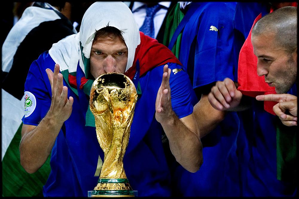 Duitsland. Berlijn, 09-07-2006<br /> WK Voetbal Finale: Italie-Frankrijk. <br /> Titelverdediger Frankrijk starte hoopvol tegen het altijd sterke Italie. Het had een mooi afscheid voor de franse voetballer moeten zijn maar Zinedine Zidane werd met een rode kaart van het veld werd gestuurd na het geven van een kopstoot aan Mazzarati. De fransen hielden lang stand maar na de verlenging en strafschoppen gingen de Italianen lachend met de Wereldbeker naar huis. Francesco Totti bejubbelt de wereldbeker na de winst op medefinalist Frankrijk. Rechts aanvoerder fabio Cannavaro. Italie wint na verlenging en strafschoppen.<br /> Foto: Patrick Post / Sportstation