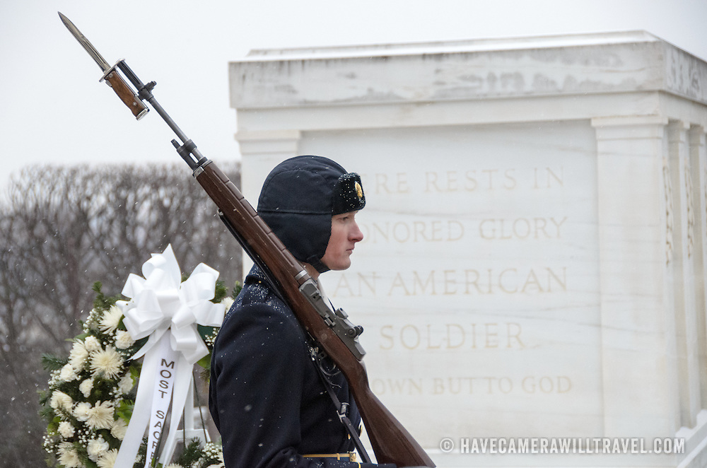 A soldier takes part in the changing of the guard ceremony at the Tomb of the Unknowns at Arlington National Cemetery in the snow. He is passing in front of the actual tomb, with the inscribed inscription.