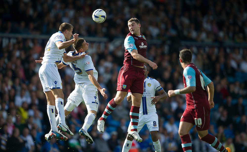 Burnley's Sam Vokes in an aerial dual with Leeds United's Scott Wootton(L) and Jason Pearce<br /> <br /> Photo by Stephen White/CameraSport<br /> <br /> Football - The Football League Sky Bet Championship - Leeds United v Burnley - Saturday 21st September 2013 - Elland Road - Leeds<br /> <br /> © CameraSport - 43 Linden Ave. Countesthorpe. Leicester. England. LE8 5PG - Tel: +44 (0) 116 277 4147 - admin@camerasport.com - www.camerasport.com
