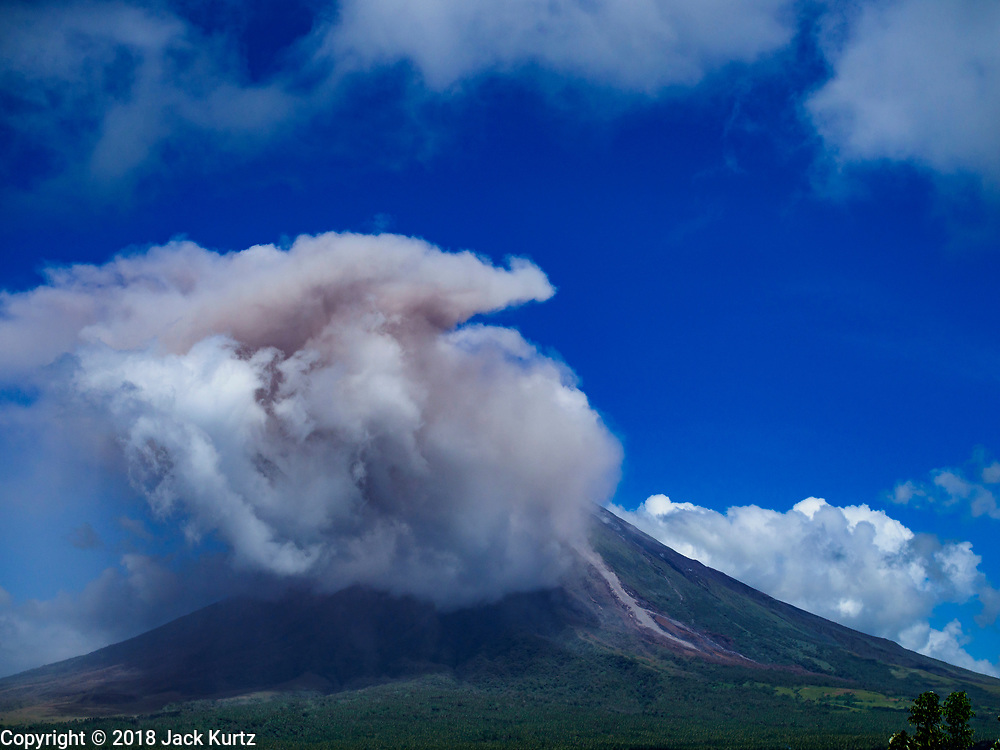 """22 JANUARY 2018 - CAMALIG, ALBAY, PHILIPPINES: Smoke and ash pour out of the cone at the Mayon volcano. There were a series of eruptions on the Mayon volcano near Legazpi Monday. The eruptions started Sunday night and continued through the day. At about midday the volcano sent a plume of ash and smoke towering over Camalig, the largest municipality near the volcano. The Philippine Institute of Volcanology and Seismology (PHIVOLCS) extended the six kilometer danger zone to eight kilometers and raised the alert level from three to four. This is the first time the alert level has been at four since 2009. A level four alert means a """"Hazardous Eruption is Imminent"""" and there is """"intense unrest"""" in the volcano. The Mayon volcano is the most active volcano in the Philippines. Sunday and Monday's eruptions caused ash falls in several communities but there were no known injuries.    PHOTO BY JACK KURTZ"""
