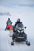 UNIS student Kiya Riverman (front) and Emilia Piasecka wait seated in their snowmobiles in Sassendalen, Svalbard on a class field trip to Tunabreen.