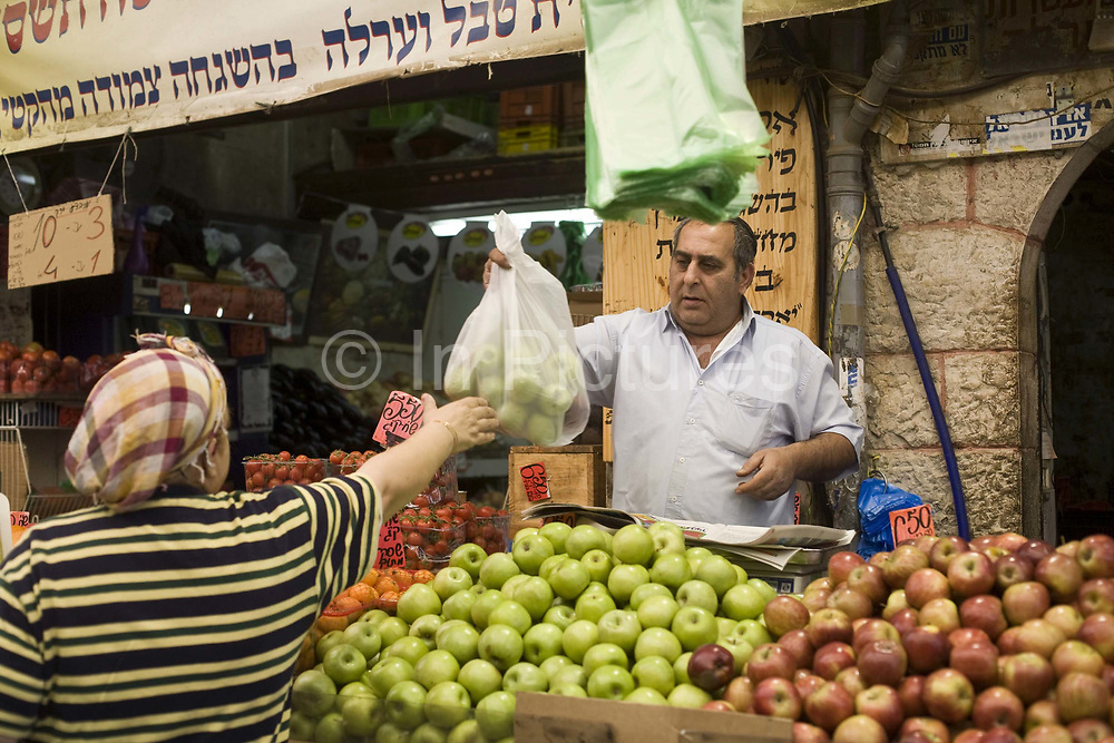 A trader on a stall at the Mahane Yahuda Market sells a woman some fruit in a bag, Jerusalem, Israel