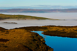 © Licensed to London News Pictures. 26/11/2020.  Builth Wells, Powys, Wales, UK. A cloudless blue sky is reflected in a lake on the Mynydd Epynt near Builth Wells in Powys. Fog hangs in the valleys and there is frost on the ground after temperatures drop to freezing last night near Builth Wells in Powys, UK. Photo credit: Graham M. Lawrence/LNP