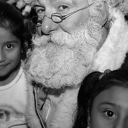 Russell Bissonnette poses with children at the annual Miramar Restaurant Christmas party on Monday, Dec. 20, 2004 in Half Moon Bay. Bissonnette has performed at the party for 15 years. The Miramar is located in Half Moon Bay just off of Coastal Highway 1 on the waterfront. Bissonnette has 30 years of experience as Santa Claus. In 1978 he created a training video for Western Temp. The video outlined how to be a good non-religious Santa, how to dress and how to answer children's questions...Photo by David Calvert<br />