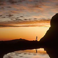 A hiker greets the dawn beside a small lake under Mount Whitney in California's Sierra Nevada.